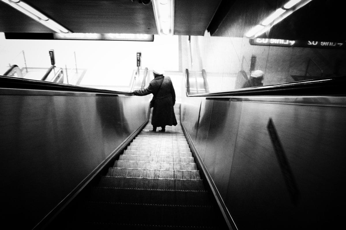 ältere frau auf einer rolltreppe beim karlsplatz in wien