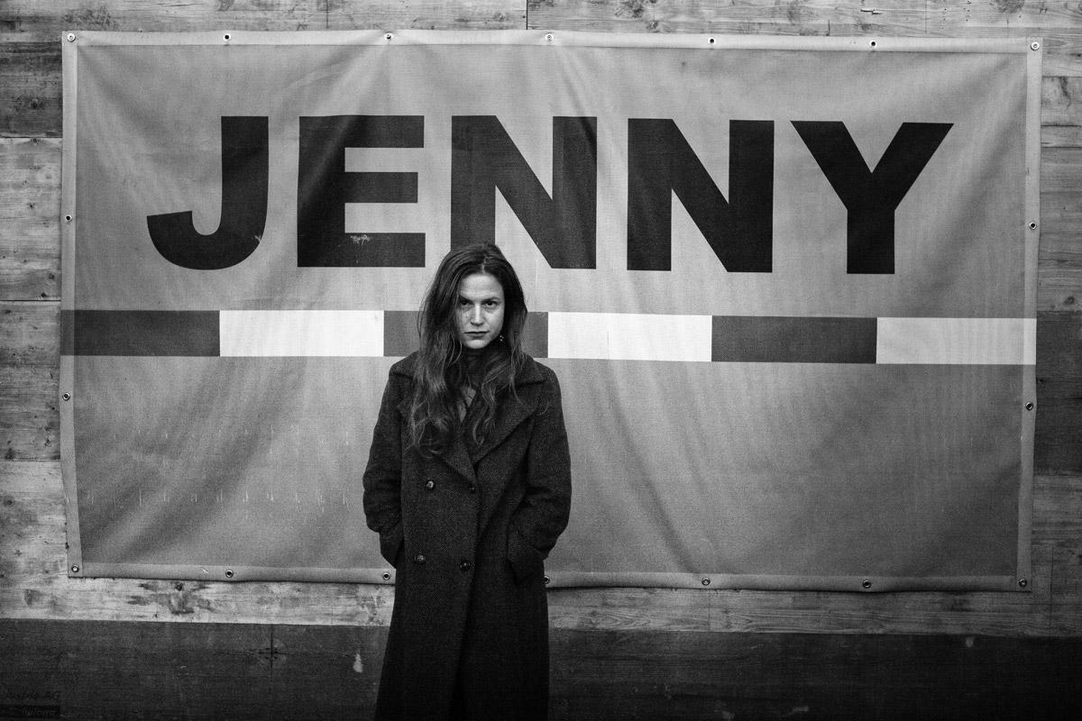 die schauspielerin ann-katrin doering vor einem bauschild der firma jenny