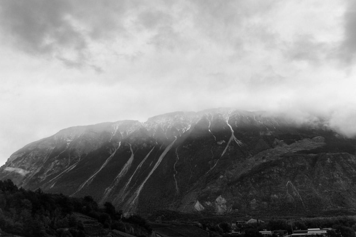 walliser berghang oberhalb von sierre mit schneisen, tannen und wolken im regenwetter