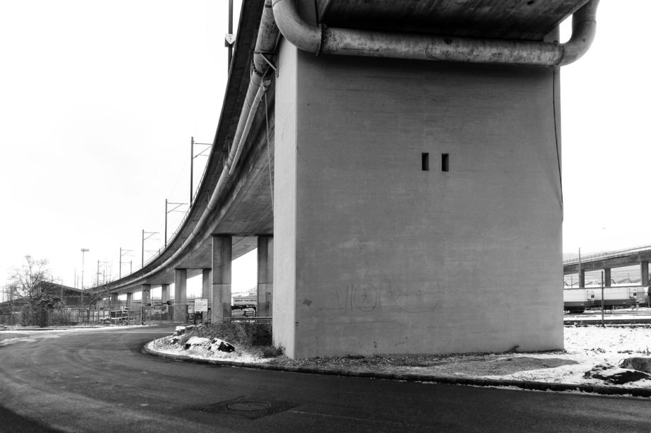 eisenbahnbrücke überquert eine strasse in einem industriequartier